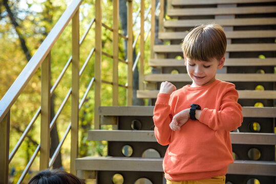 A cute boy wearing stylish shirt stay near school, looking at his smart watch touching the screen. A child using electronic device. Lifestyle concept