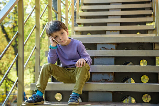 Closeup portrait, worried, sad young child, boy talking on phone to someone, looking unhappy, isolated outdoors background. Negative human emotions, facial expressions, feeling, reaction Communication