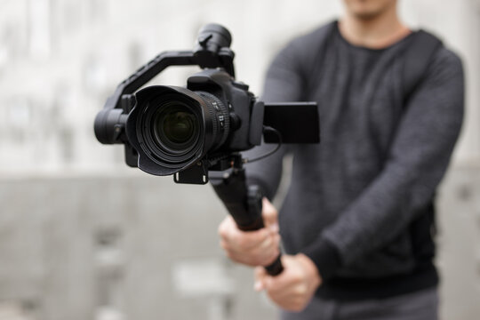 filmmaking, hobby and creativity concept - close up of modern dslr camera on 3-axis gimbal in male hands