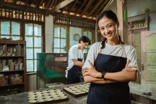 Smiling asian girl in apron looking to the camera with baking sheet cake background on the table