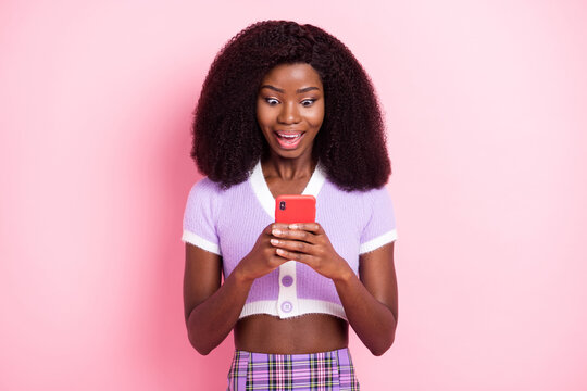 Portrait of pretty amazed funky addicted cheerful wavy-haired girl using device browsing smm media isolated over pink pastel color background
