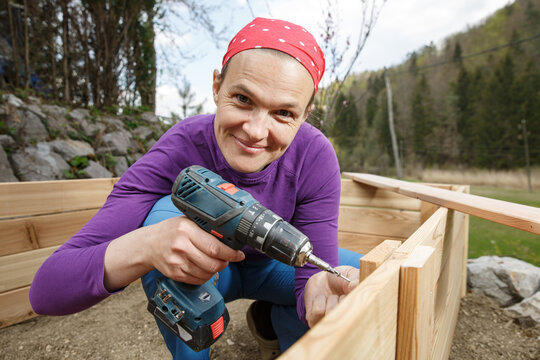 Woman screwing wooden frame for a raised garden bed.