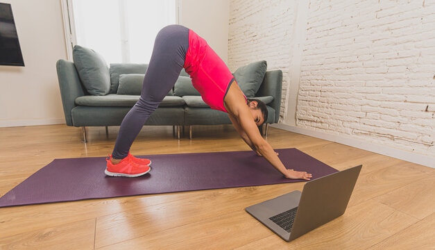 Attractive woman on laptop in virtual online fitness class working out at home