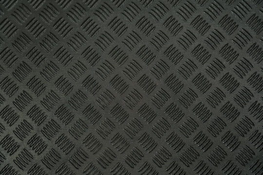 Closeup top view flatlay stock photography of texture of black protective hdpe rug or mat for boot of car