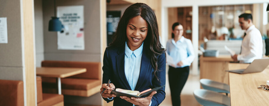 Smiling African American businesswoman walking through an office writing notes