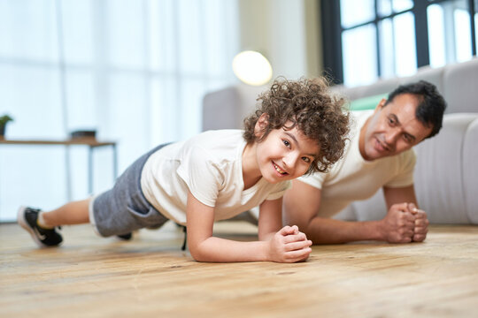 Doing Sports. Cheerful latin boy smiling at camera while exercising together with his sportive middle aged father, doing plank at home