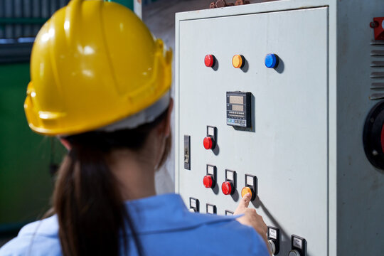 Female engineer will pressing the yellow button on controller box of beverage industry