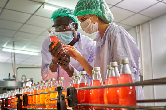 African and Caucasian specialists of beverage check quality of red juice in automatically product line of beverage industry