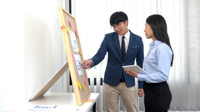 Professionals Businessman and businesswoman discussing over sticky notes to share idea on board  in office, brainstorming concept.