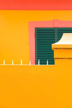 Colorful vintage building with green window shutters on yellow wall