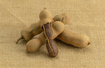 Fototapete - Pile of peeled and whole ripe tamarind on sackcloth.