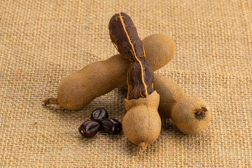 Fototapete - Whole and peeled ripe tamarind with seeds on sackcloth.Tamarind is a good laxative food for human.