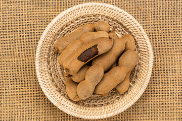 Fototapete - Top view of tamarind in a bamboo basket on sackcloth. Ripe whole and peeled tamarind in bammboo basket.