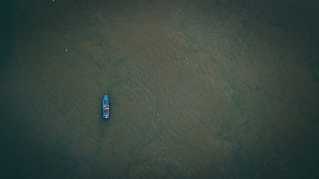 Overhead shot of a blue boat in the water