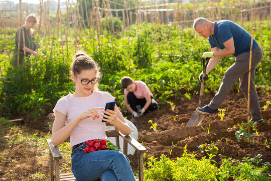 Teenage girl engaged in gardening with family using phone sitting in chair in garden having break