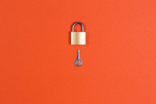 Lock and key on orange background
