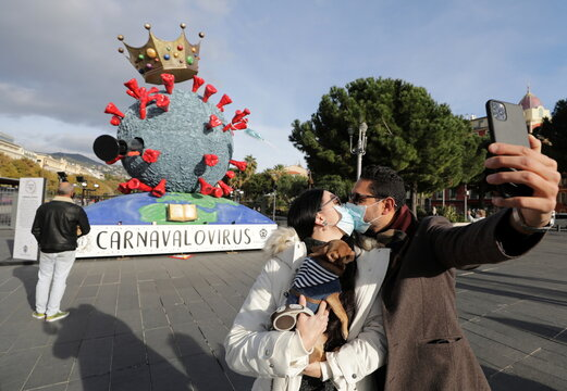 A couple share a kiss as they take a selfie in front of a Carnival float depecting the novel coronavirus in Nice