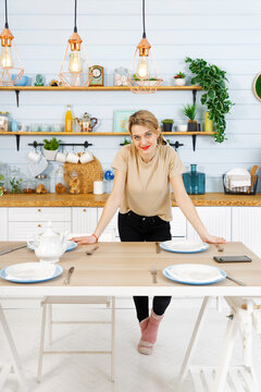 Young pretty girl stands in the home kitchen with her hands resting on the table
