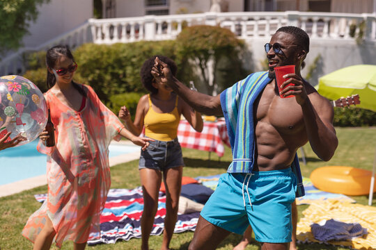 Diverse group of friends having fun and dancing at a pool party