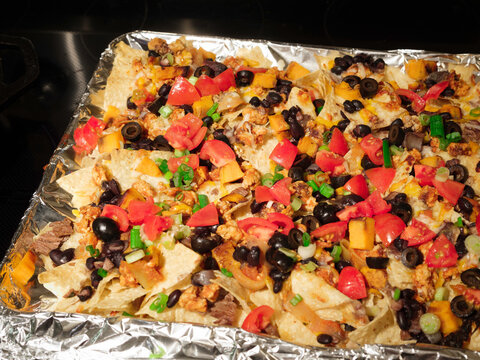 Homemade sheet pan loaded nachos with olives, fresh tomatoes, scallions, cheese, black beans, and meat