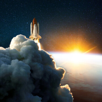 Rocket launch, lift off at amazing sunset. Space shuttle in the space near Earth with yellow sunrise. Clouds and sky on background. success start cosmos mission