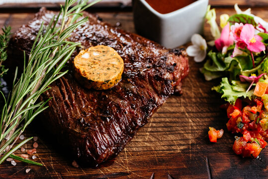 Grilled Steak on slate serving platter with vegetables herbs and