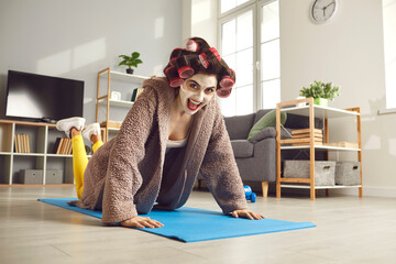 Fototapeta Happy young woman doing knee push-ups during fitness workout at home. Funny housewife in hair curlers and beauty face mask exercising on sports mat and looking at camera. Keeping fit concept obraz