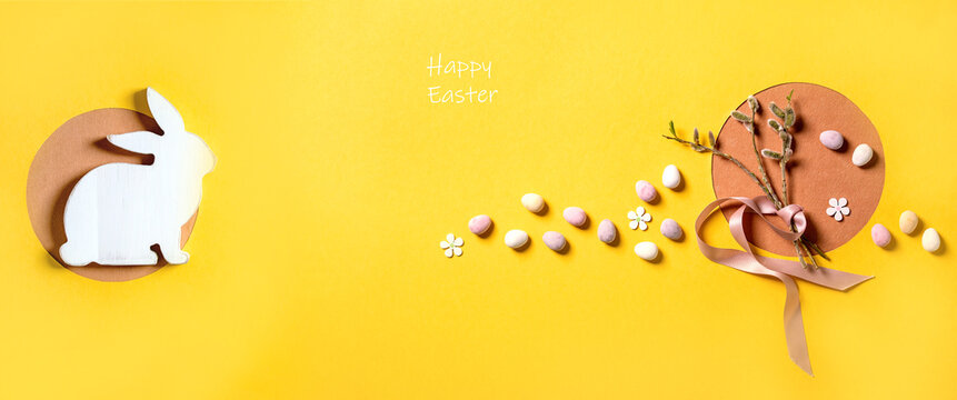 Easter greeting card with blossom willow branches, colorful candies and white rabbit on bright orange yellow background. Happy Easter inscription. Flat lay, copy space.