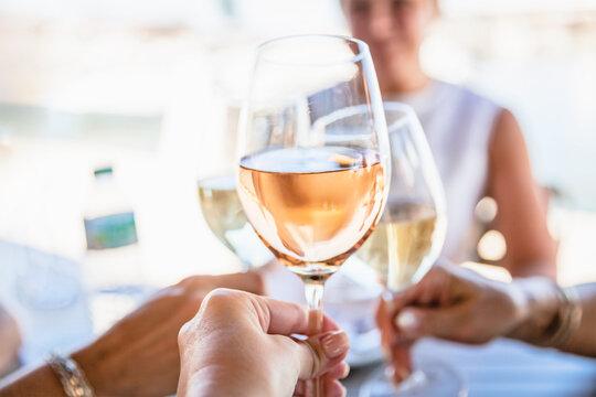 Four female friends drinking wine in street cafe
