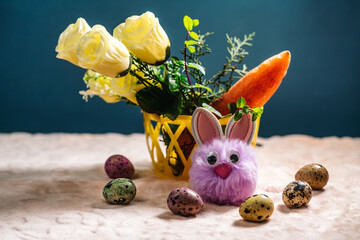 toy fluffy easter bunny sitting next to carrots, easter eggs and artificial flowers
