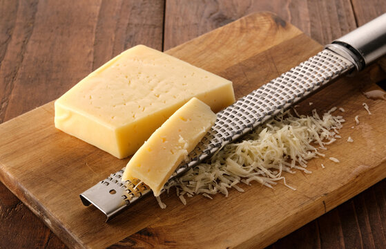 Grated cheese and grater on a wooden board