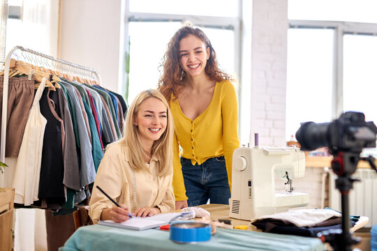 two young designers bloggers broadcast on professional camera, speaking, sharing tips, talking with subscribers, they stand by sewing machine and smiling at camera. in atelier