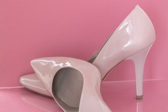 Pair of women pink patent leather high-heeled shoes on pink Pastel background. Women fashion and accessories