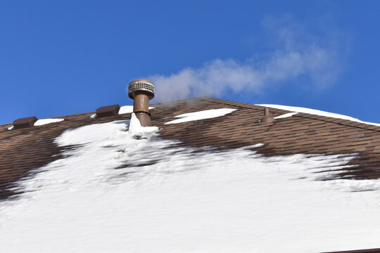 Roof Vent with Steam on a Snowy Roof