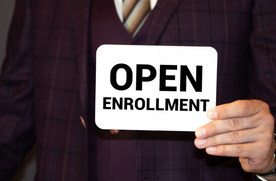 Close-up of a male doctor in gloves holding a sign with the text OPEN ENROLLMENT.