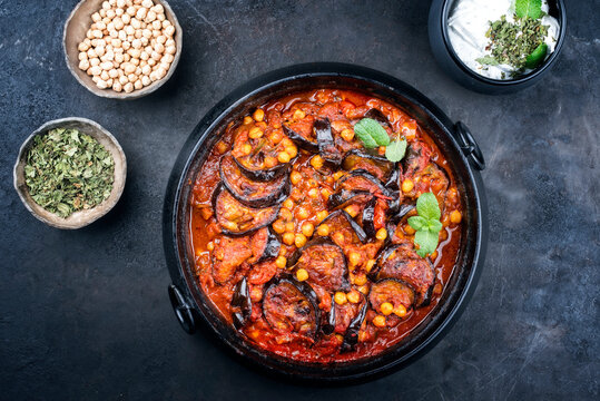 Modern style slow cooked Lebanese vegetarian eggplant stew maghmour served with chickpeas and yoghurt as top view in a design pot with copy space