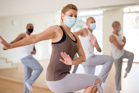 Young woman in protective face mask learning dance moves during group training. New life reality in pandemic