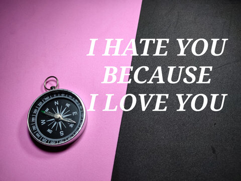 Selective focus.Compass and word I HATE YOU BECAUSE I LOVE YOU on a black and pink background.Valentine concept.Shot were noise and grain.
