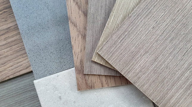 mood and tone interior material board presenting combination of wooden veneer samples and quartz stone tile samples. close up multi color and texture of veneer and artificial stone swatch.
