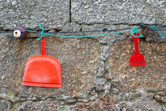 An orange plastic hand dustpan and a red plastic rake hanging from a green cord with a stone wall