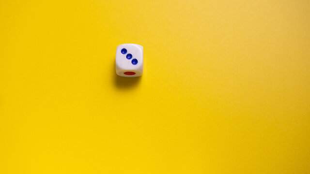 White dice with round dots number three on yellow background close-up. Concept of gambling and chance