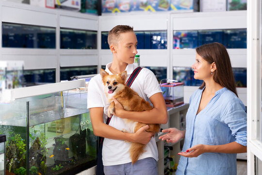Happy woman with teen boy visiting pet shop with their little dog in search of new exotic fish for home fish tank