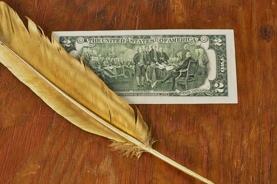 Gold quill pen and picture of signing US Declaration of independence in two dollars banknote