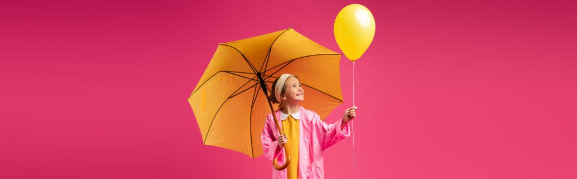 cheerful girl in raincoat holding balloon and yellow umbrella isolated on crimson, banner
