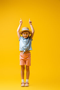 full length of cheerful child in straw hat pointing up with fingers on yellow