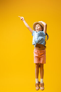 full length of shocked kid in straw hat pointing away with finger on yellow