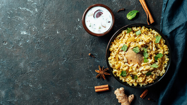Pakistani food - biryani rice with chicken and raita yoghurt dip. Delicious hyberabadi chicken biryani on plate over black textured background. Top view or flat lay. Copy space. Banner