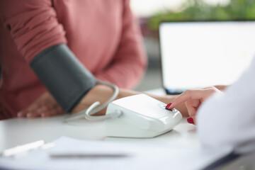 Doctor measures patient's blood pressure in medical office