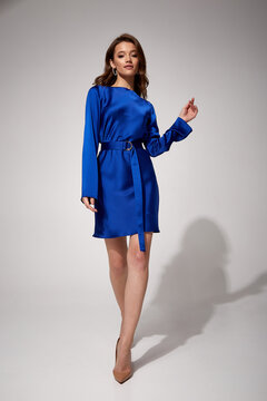 Beautiful woman fashion model makeup brunette hair perfect body shape tanned skin wear clothes summer collection organic mini blue silk dress stylish sandals shoes, accessory romantic date walk.