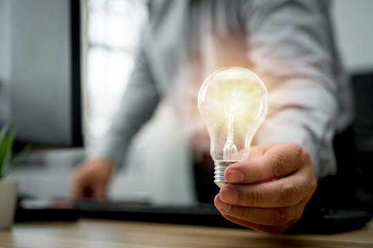 Businessman holding lightbulb and feeling happy by new innovation and ideas for success business panels. Concept of innovation creative technology ideas for Business solution